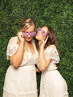 creative booth girls posing on green wall