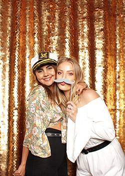 creative booth girls posing with gold sequin backdrop